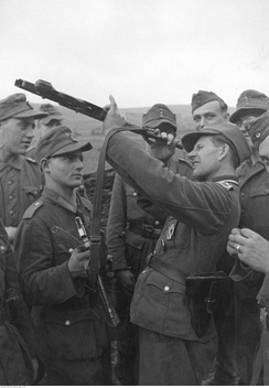 A gunsmith surrounded by soldiers inspects an StG 44 rifle barrel. Galician front, 10 October 1944