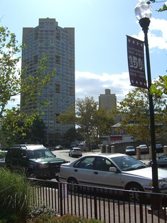 A 2009 sign on Boulevard East advertising the town's 150th anniversary. In the background is one of the three towers of the Galaxy apartments.