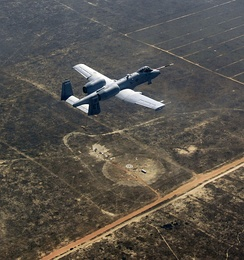 An A-10C Thunderbolt II, piloted by the 40th Flight Test Squadron, flies over what's left of a target that was successfully hit by a Laser Joint Direct Attack Munition drop on the Eglin range.