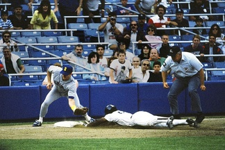 Rickey Henderson successfully steals third base as Jim Presley prepares to catch the ball.