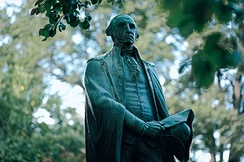 A bronze George Washington statue overlooks the campus green.