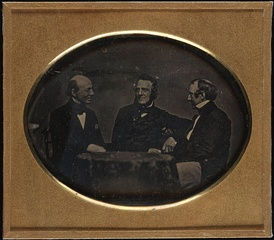 Garrison and fellow abolitionists George Thompson and Wendell Phillips, seated at table, daguerreotype, c. 1850–1851