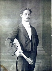 "Italian mandolin virtuoso and child prodigy Giuseppe Pettine (here pictured in 1898) brought the Italian playing style to America where he settled in Providence, Rhode Island, as a mandolin teacher and composer. Pettine is credited with promoting a style where ""one player plays both the rhythmic chords and the lyric melodic line at once, combining single strokes and tremolo.""[106]"