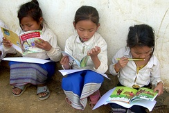 Three Laotian girls sit outside their school, each absorbed in reading a book they received at a rural school book party.