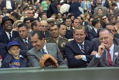 Nixon at the Washington Senators' 1969 Opening Day. To the right of Nixon is team owner Bob Short and then Baseball Commissioner Bowie Kuhn. Marine Corps Aide to the President Jack Brennan sits in uniform behind Nixon.