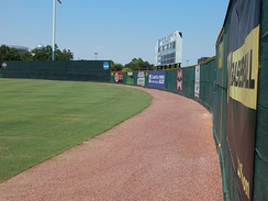 The warning track abutting the outfield fence of Husky Field, used by the Houston Baptist Huskies baseball team
