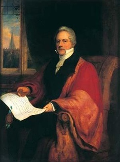 A man in red academic robes sitting in a chair with a city scene visible through a window