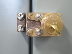 This is a trapped-key interlock on the door of an electrical switchgear cabinet. It is attached with one-way security screws to discourage casual removal, which would defeat the interlock scheme.