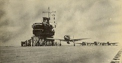 Under overcast skies, an A6M Zero fighter leads the air group launch off the deck of Shōkaku the morning of 8 May.
