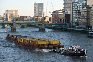 Barges towed by a tugboat on the River Thames in London, England, UK