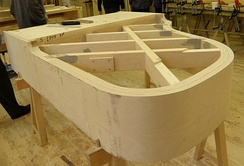 Outer rim of Estonia grand piano during the manufacturing process. The underside is facing upward, showing the thick beams that will support the rim and frame.