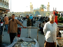 Souq in Al-Kāẓimiyyah with the shrine in the background.