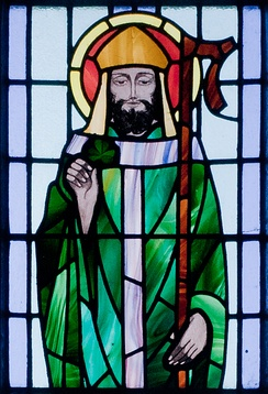 St. Patrick depicted with shamrock in detail of stained glass window in St. Benin's Church, Wicklow, Ireland