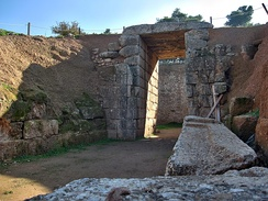 The Lion Tholos Tomb at Mycenae. Of note are the ashlar stomion (of conglomerate) and dromos while the chamber itself remains made of smaller stones, placing the tomb in Wace's second group