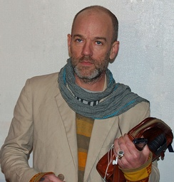 Michael Stipe looking to the left of the camera, holding a bag and digital media player