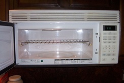 A microwave oven with a metal shelf