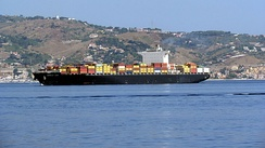 A cargo ship cruises towards the Strait of Messina