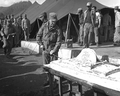 "Col Lewis B. ""Chesty"" Puller cuts the Marine Corps birthday cake in 1950, during a brief reprieve in battle during the Korean War."