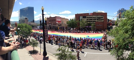 The rainbow flag at the back of the 2014 Utah Pride parade. People watch from the street, from rooftops, and from a parking structure.