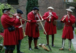A re-created wait, an ensemble of loud instruments suited to playing outdoors. Centre, a sackbut.