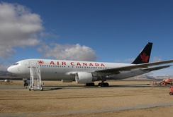 Side view of a parked Air Canada twin-engine jet in the desert, with stairs mounted next to the aircraft's forward door