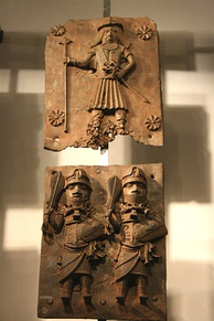 Two brass plates depicting a bearded Portuguese soldier before 1500 on top and Benin warriors at the bottom