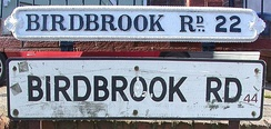 "Street name signs on Birdbrook Road, Great Barr, Birmingham, showing old ""Birmingham 22"" (top) and modern ""B44"" postcodes."