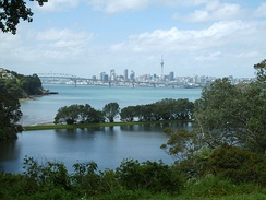 A view over Chelsea Sugar Refinery's lower dam towards Auckland Harbour Bridge and the CBD