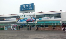 The sign with the name of the railway station in Jecheon — at the top, a writing in hangul, the transliteration in Latin script below  using the Revised Romanization and the English translation of the word 'station', along with the hanja text.