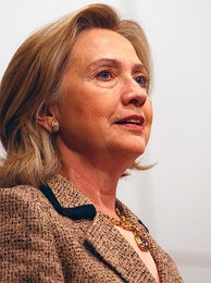 Informal pose of Clinton, in which she is wearing a beige wool jacket and facing toward the right. The angle at which Clinton is photographed is from her bottom right side.