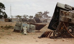 Pieces of a destroyed tank, notably the gun turret, lie on a sandy landscape.