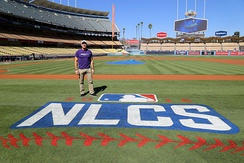 Billy Bean stands by the NLCS logo at Dodger Stadium in 2016