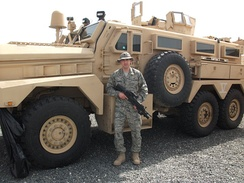 A member of the United States Air Force stands in front of an MRAP in Southwest Asia.