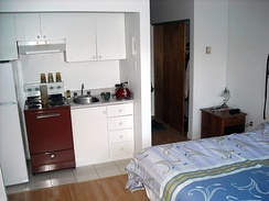 Studio apartment, showing double bed, kitchenette, and entrance way with sliding door to closet