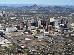 photo taken from an aircraft showing the tall buildings of downtown Phoenix, with the mountains which surround the city in the background.