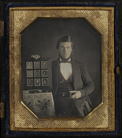 Portrait of a Daguerreotypist Displaying Daguerreotypes and Cases pictured in an airtight frame.