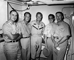 "Medical debriefing of Major John H. Glenn, Jr., USMC after orbital flight of Friendship 7 on 20 February 1962 aboard the aircraft carrier USS Randolph (CVS-15). The debriefing team for Lt. Colonel Glenn (center) was led by Commander Seldon C. ""Smokey"" Dunn, MC, USN (FS) (RAM-qualified) (far right w/EKG in hands)."
