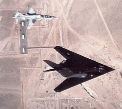An F-117 Nighthawk with a T-38 Talon chase plane flying over Tonopah Test Range Airport.