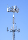 (left) Modern cellphone. (right) Cellular phone tower shared by antennas belonging to 3 different networks.