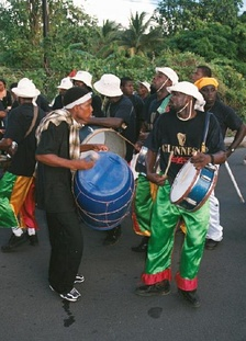 Band members wearing black T-shirts and white hats play drums in the street. Tropical foliage in the background.