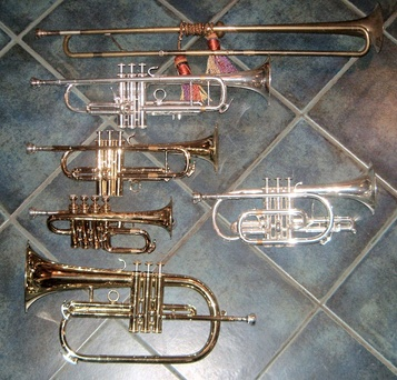 Six high brass instruments Left, from top: A reproduction baroque trumpet in D, a modern trumpet in B♭, a modern trumpet in D, a piccolo trumpet in B♭ (octave higher), and a flugelhorn in B♭. Right: a cornet in B♭.