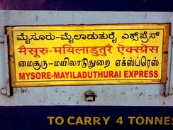 A Train name found in South India written in four languages: Kannada, Hindi, Tamil and English.  Boards like this are common on trains which pass through two or more states where the languages spoken are different.