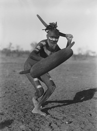 A Luritja man demonstrating method of attack with boomerang under cover of shield (1920)