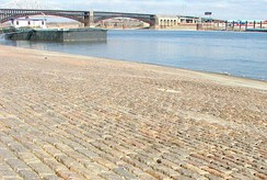 Granite from this region was used for cobblestones on the St. Louis wharf and in the piers of the Eads Bridge (background).