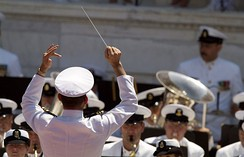 A military conductor leads the U.S. Navy band during Memorial Day ceremonies held at Arlington National Cemetery.