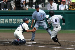 A catcher (left) drops to both knees to block the plate from an opposing baserunner during a Japanese high school baseball game
