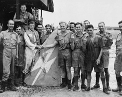 Buffalo pilots of No. 488 Squadron RNZAF based at Kallang display the tail fin of a Japanese Ki-46 aircraft of 81st Sentai which they shot down over Johore, Malaya, January 1942.