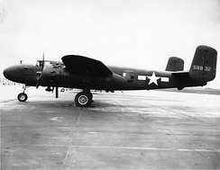 Black and white photo of an early bomber parked perpendicular to camera, facing left, rearward of the wing is a star in front of horizontal stripes.