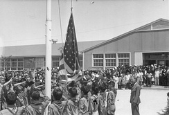 Boy Scouts at the Granada War Relocation Center raise the flag to half-mast during a Memorial Service for the first six Nisei soldiers from this Center who were killed in action in Italy. The service was attended by 1,500 Amache internees. -- August 5, 1944.