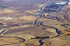 An aerial view of the Delta–Mendota Canal (left) and the California Aqueduct (right), at the Interstate 205 crossing west of Tracy, conveying water from Northern to Southern California